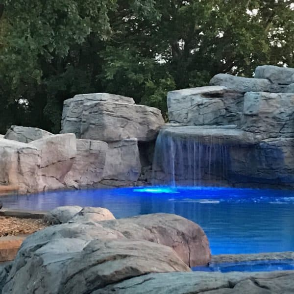 A water feature that has water falling in an illuminated pool with blue lights at the bottom. located in Muenster Texas.