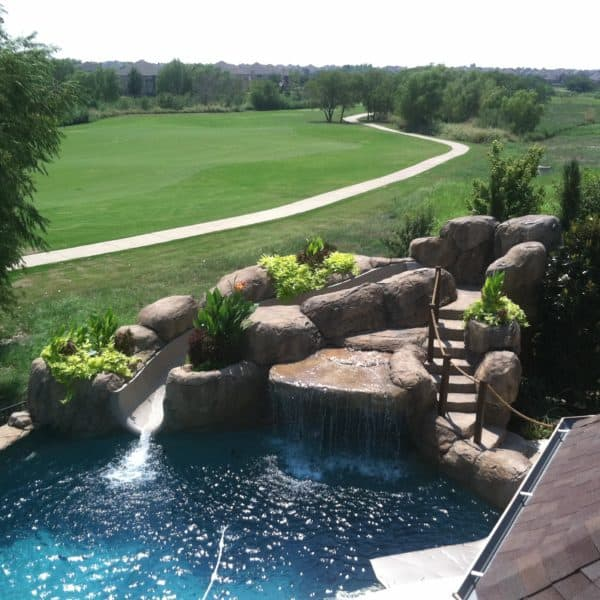 A water feature that has stairs leading up to the top where a slide flows into a swimming pool. Frisco Texas.