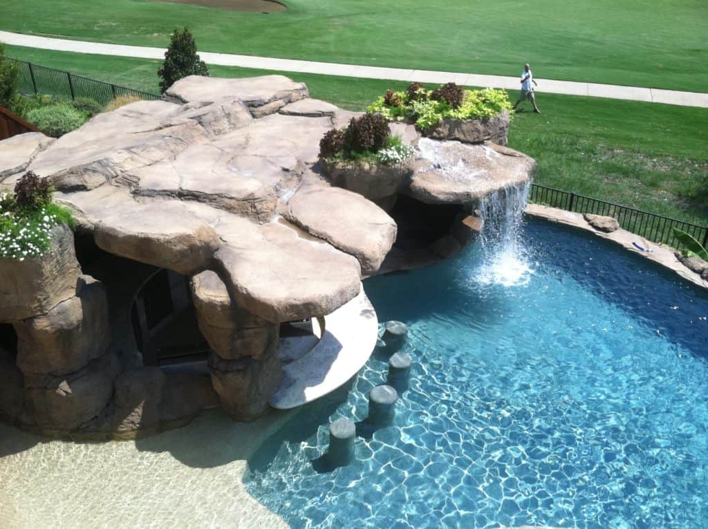 A water feature that has a cave behind a waterfall that falls into a swimming pool located in Plano Texas.