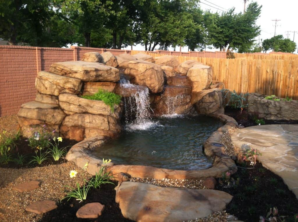 Rushing waters from the waterfall that flows into the pond below create a calming effect as the homeowners sit in their backyard.