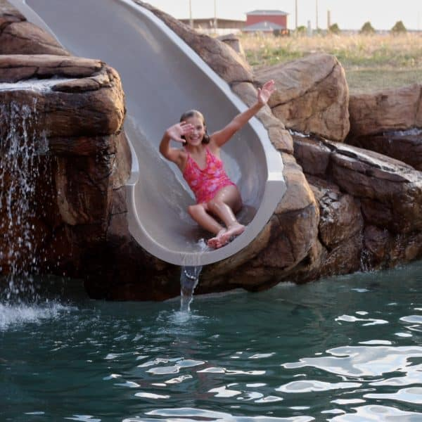 A child sliding into a swimming pool from a water feature in Lawton Texas.