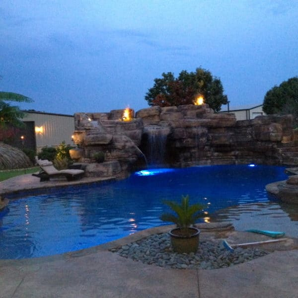 A water feature at night with fire pits illuminating the waterfall. Rockwall Texas.