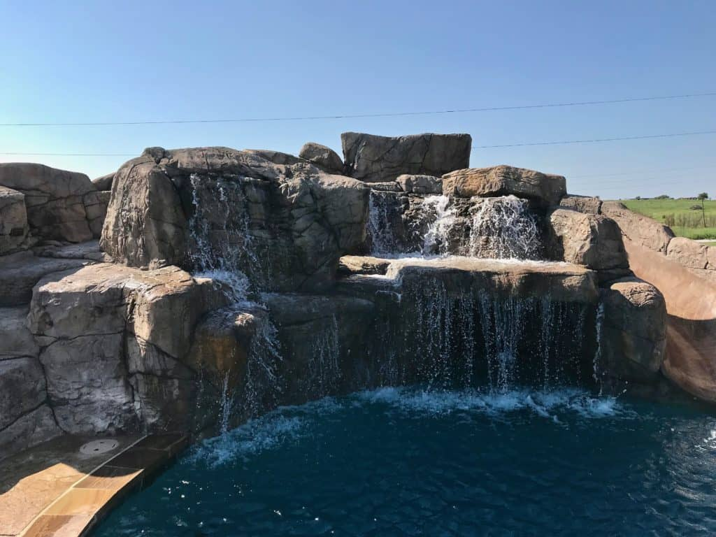 Sparkling waterfalls cascade over the grotto, dripping to the pool below. The artificial rock steps lead to a slide where kids enjoy taking a plunge into their pool. Muenster, TX