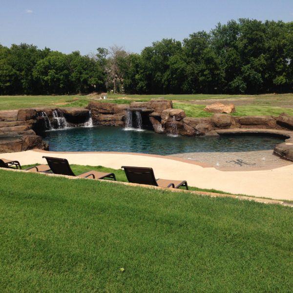An artificial water feature with water running into a swimming pool. Denton Texas