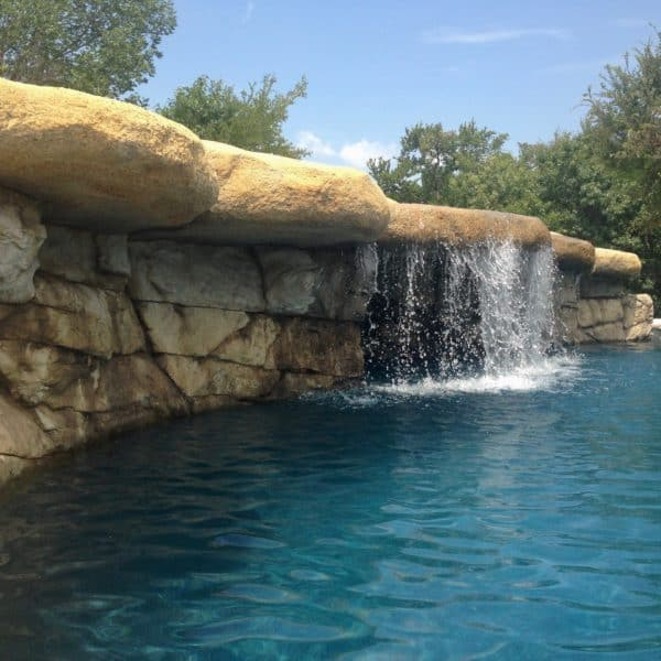 An artificial waterfall with water falling into a pool in Fort Worth Texas.
