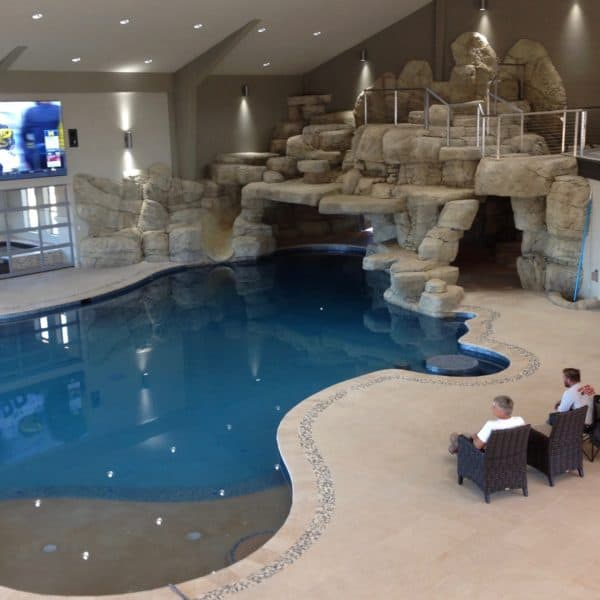 A picture of a large indoor water feature that sits above a pool while two men are watching a TV screen that is mounted to the wall. Located in Oklahoma City, Oklahoma.
