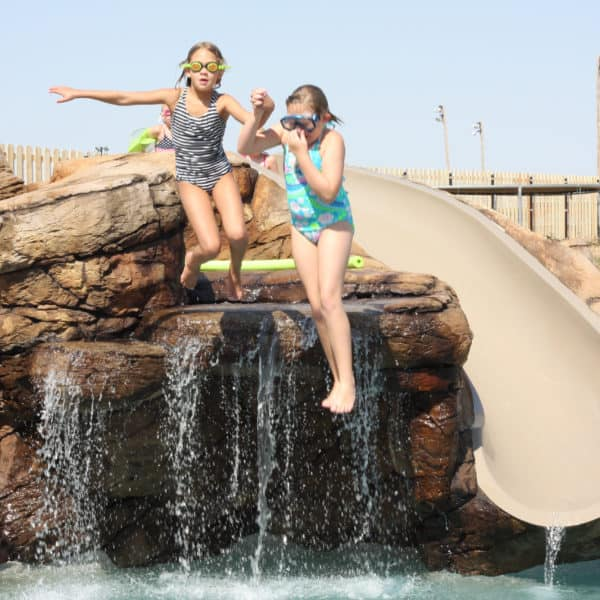 A picture of two children jumping off an artificial waterfall with a slide into a swimming pool. Located in Oklahoma City Oklahoma.