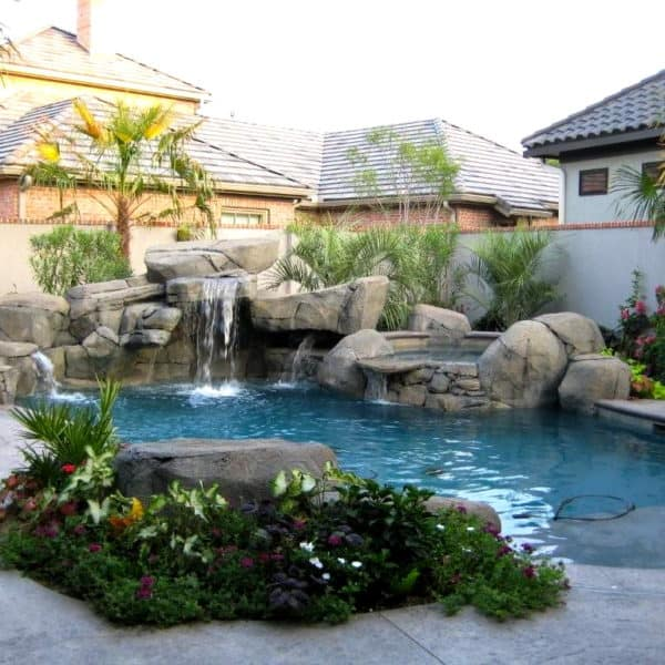 An artificial waterfall in a walled backyard in Fort Worth Texas.