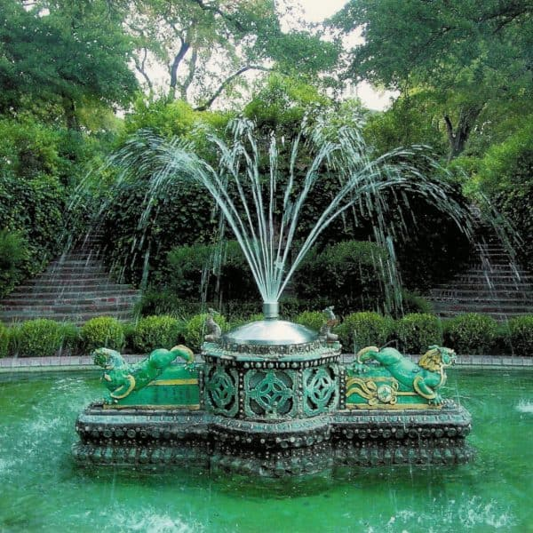 An oriental styled fountain made out of artificial rock falling into a pond in Weatherford Texas.