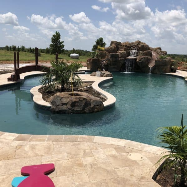 A waterfall that falls into a pool that has a lazy river with a bridge over it located in Bowie Texas.