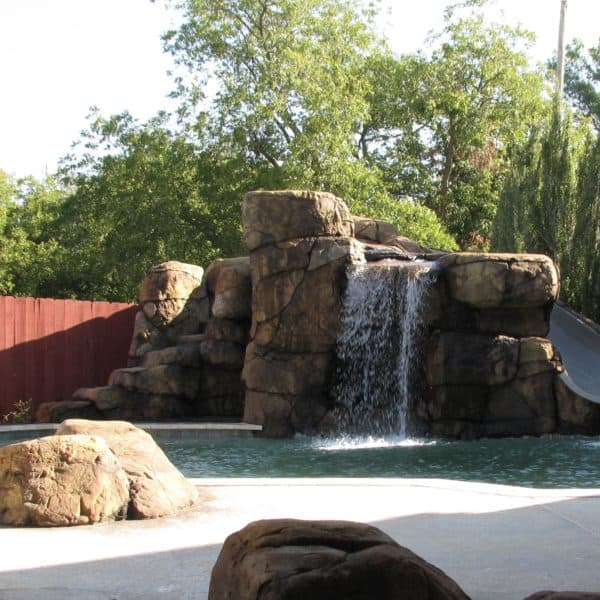 A waterfall with steps going to a slide at the top flowing into a swimming pool in Muenster Texas.