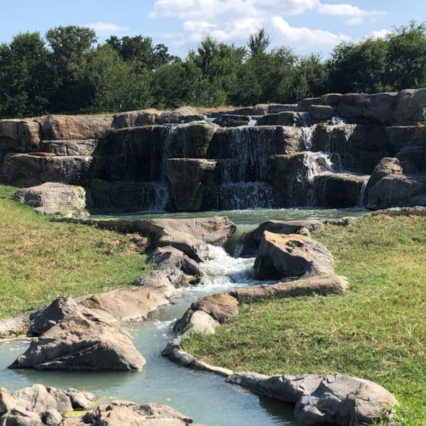 A large waterfall running into a stream that flows down around boulders located in Decatur Texas.