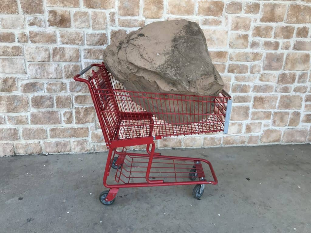 An artificial boulder placed in a shopping cart in front of a stone wall.