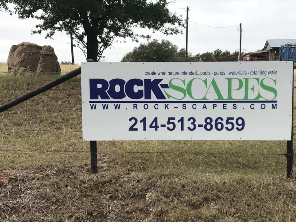 A sign of rock-scapes on a fence with a boulder in the background of the photo.